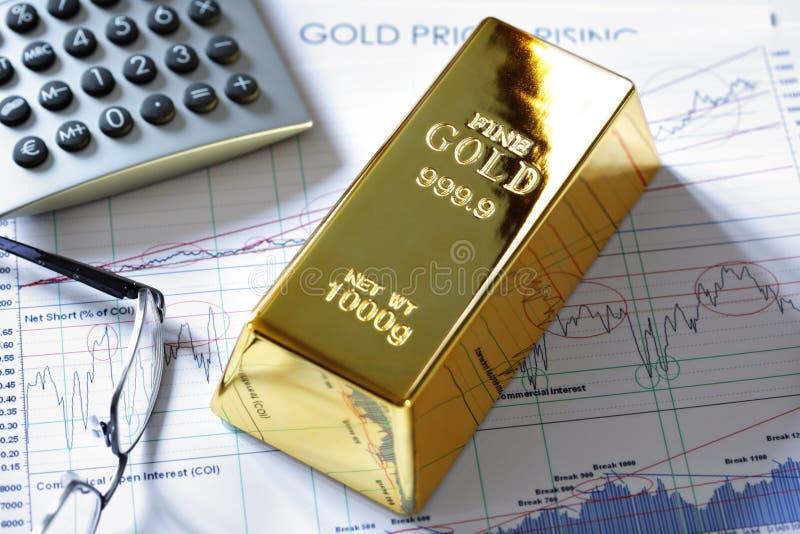 Barra del lingote de oro en una carta de los valores de bolsa fotos de archivo