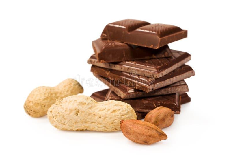 Barra di cioccolato rotta con le arachidi nelle coperture fotografia stock