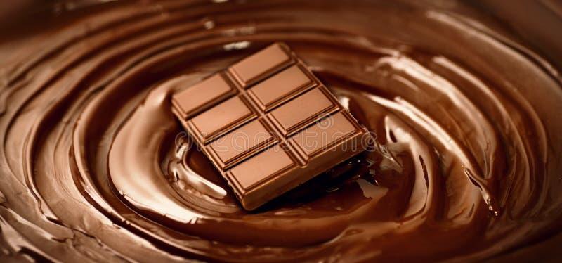 Barra di cioccolato sopra il fondo fuso del liquido di turbinio del cioccolato fondente Contesto di concetto della confetteria fotografia stock