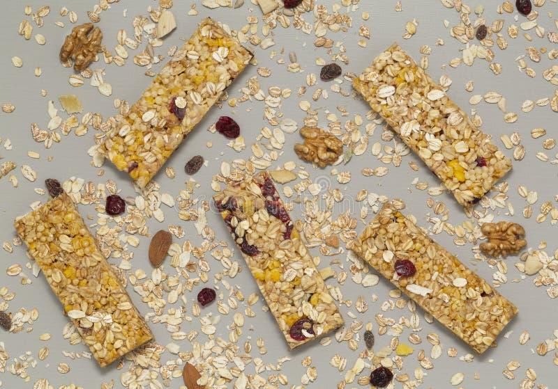 Barra di Granola Barra di granola del cereale con i dadi, la frutta e le bacche su una tavola di pietra grigia Spuntino dolce san fotografia stock libera da diritti