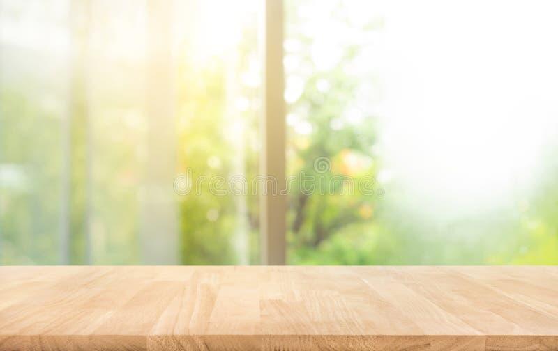 Barra di legno del contatore del piano d'appoggio su sfuocatura della finestra con il bello giardino nel fondo di mattina fotografia stock libera da diritti
