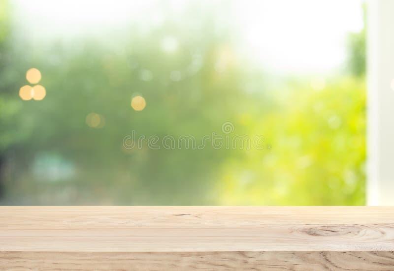 Barra di legno del contatore del piano d'appoggio su sfuocatura della finestra con il bello giardino nel fondo di mattina fotografie stock libere da diritti