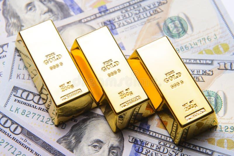 Barra di oro con le banconote in dollari dell'americano cento fotografia stock