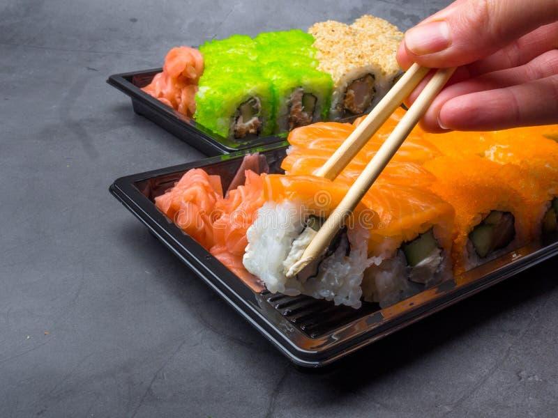 Barra di sushi saporita, mangiante i sushi con i bastoncini Insieme del rotolo di sushi di California con il salmone, verdure, pe fotografie stock libere da diritti