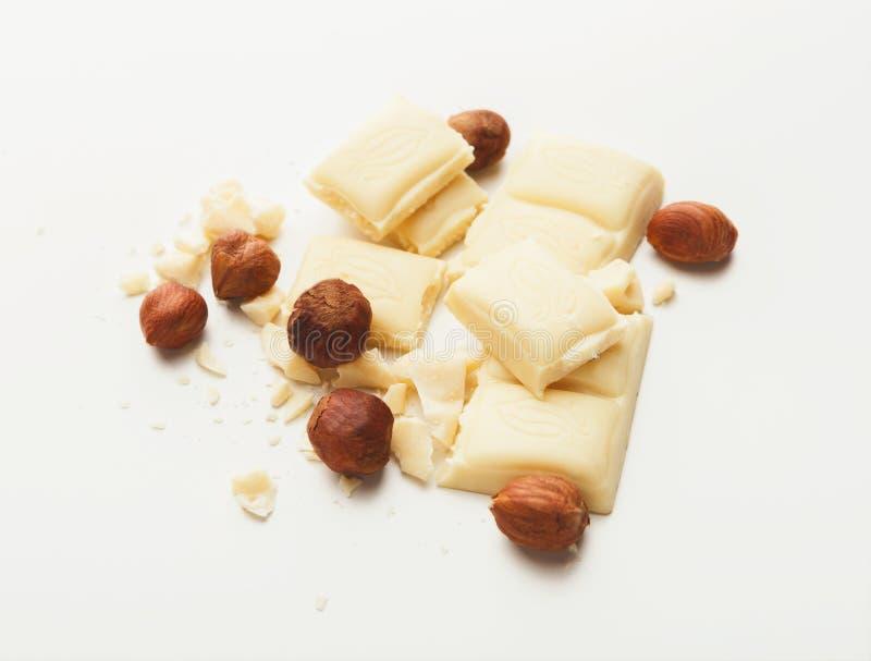 Barra e avelã brancas de chocolate quebrada isoladas fotografia de stock royalty free