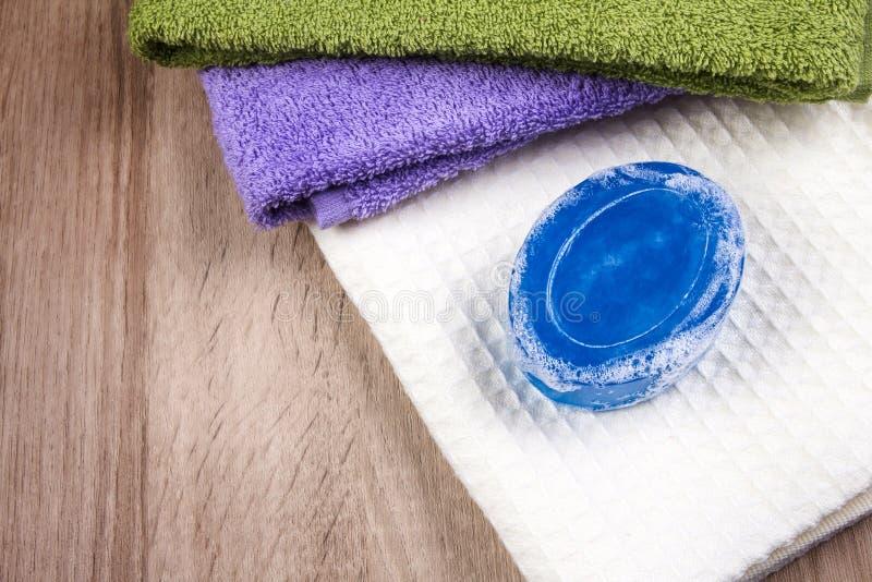 Barra e bolla naturali del sapone con l'asciugamano di bagno su fondo di legno fotografia stock libera da diritti