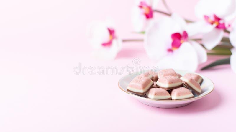 Barra e flor cor-de-rosa de chocolate no fundo cor-de-rosa Chocolate novo do rubi Sobremesa doce cor-de-rosa nova foto de stock royalty free