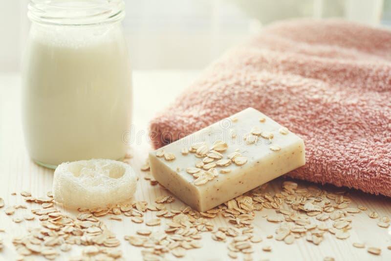 Barra hecha a mano del jabón de la leche y de la miel, toalla suave, lufa, escamas de la avena y botella de champú de la leche imagen de archivo libre de regalías