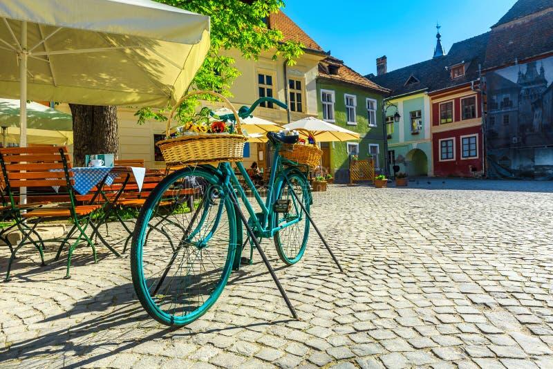 Barra medieval magnífica y calle pavimentada, Sighisoara, Rumania del café de la calle imagenes de archivo