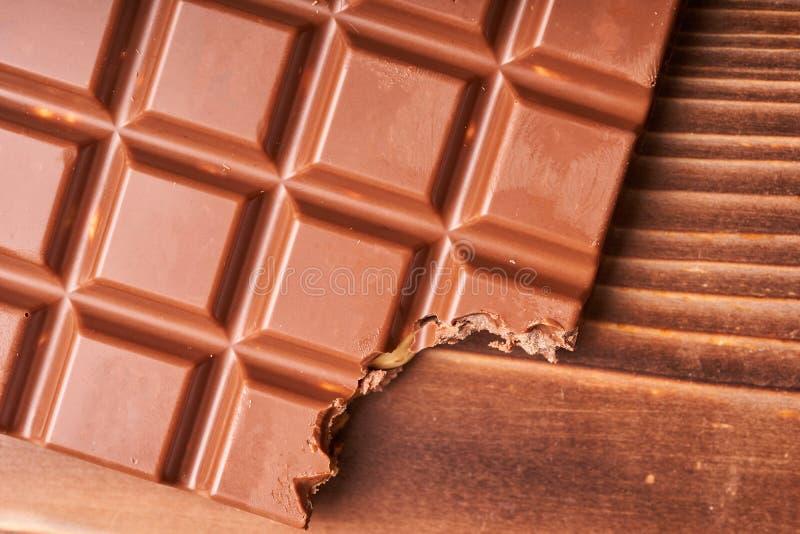 Barra mordida del chocolate con leche en un fondo de papel coloreado foto de archivo libre de regalías