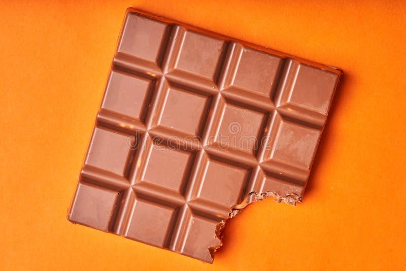Barra mordida del chocolate con leche en un fondo de papel coloreado imagenes de archivo