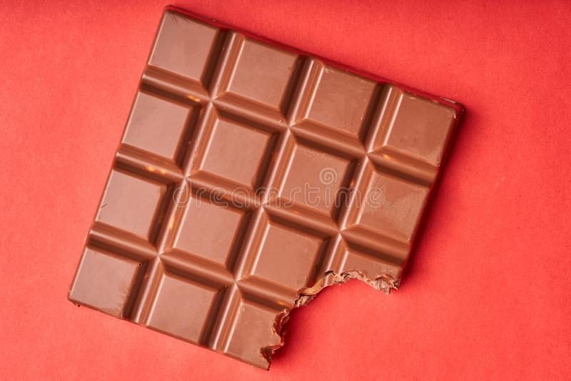 Barra mordida del chocolate con leche en un fondo de papel coloreado fotografía de archivo libre de regalías