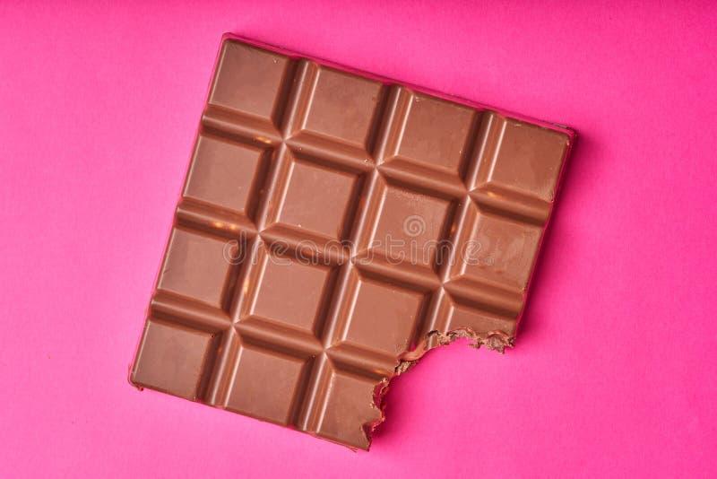 Barra mordida del chocolate con leche en un fondo de papel coloreado imágenes de archivo libres de regalías