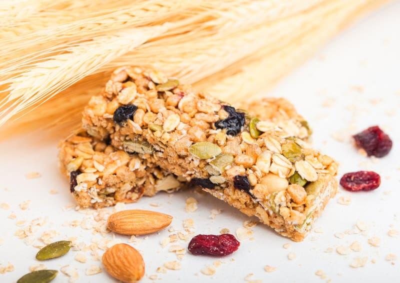 Barra organica casalinga del cereale del granola con i dadi e la frutta secca su fondo bianco con l'avena ed il grano crudo immagini stock