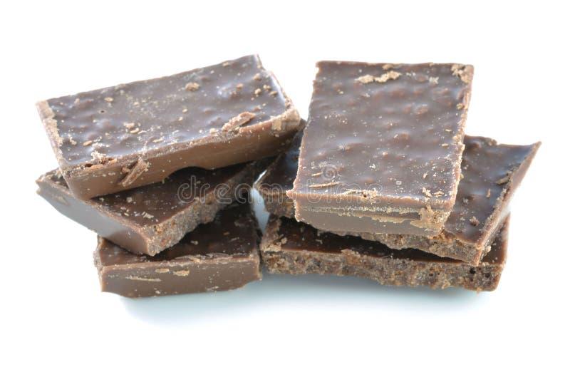 Barra quebrada del chocolate con leche aislada en el fondo blanco imagen de archivo