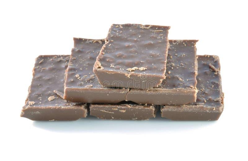 Barra quebrada del chocolate con leche aislada en el fondo blanco imagenes de archivo