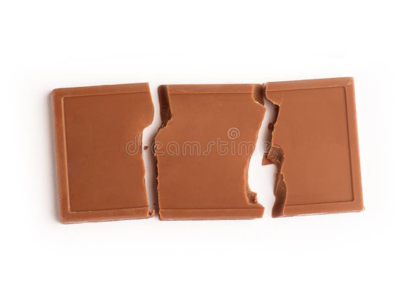 Barra quebrada del chocolate con leche en el fondo blanco fotos de archivo