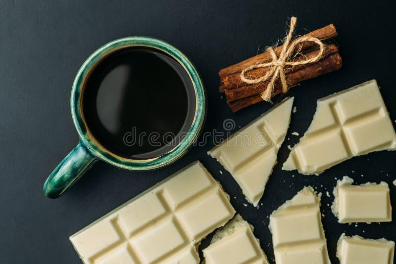 Barra quebrada do chocolate, da canela e da xícara de café brancos uma tabela preta, vista superior imagem de stock royalty free