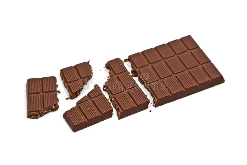 Barra rota del chocolate con leche con las avellanas aisladas en blanco fotografía de archivo libre de regalías