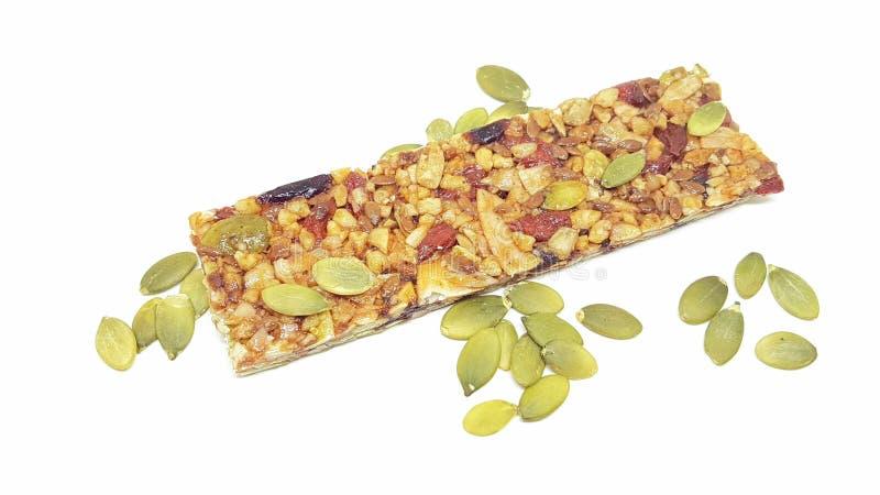 Barra suave libre del gluten orgánico del paleo con los frutos secos y el bocado sano de las semillas aislados en el fondo blanco imágenes de archivo libres de regalías