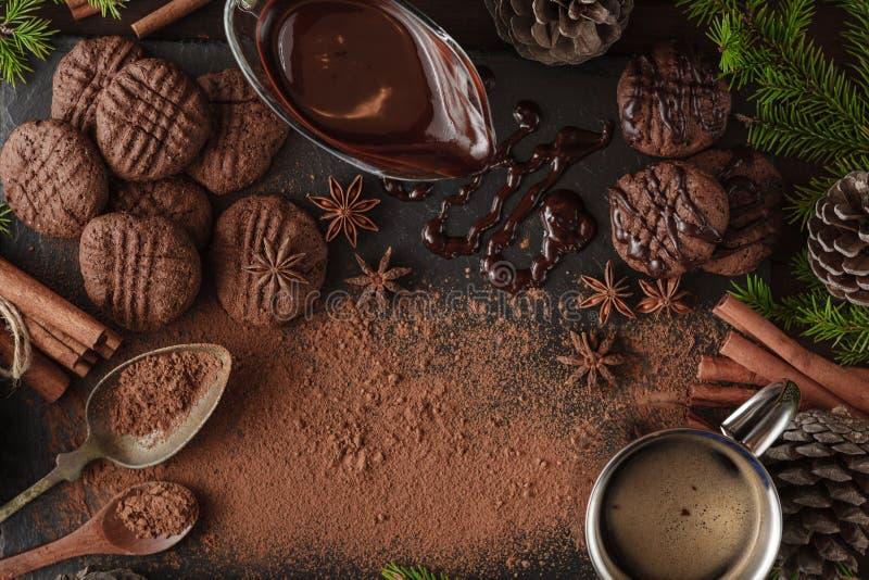 Barra y especias quebradas de chocolate en el tablero de piedra fotos de archivo