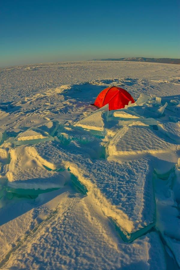 A barraca alaranjada está apenas entre os montes e o Lago Baikal do gelo imagens de stock