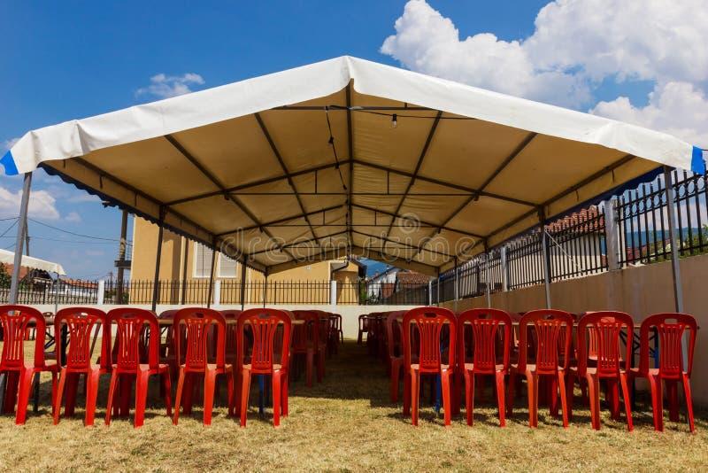 Barraca branca do entretenimento com as cadeiras plásticas vermelhas imagens de stock royalty free