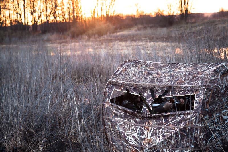 Barraca da caça com os caçadores no campo rural imagens de stock royalty free