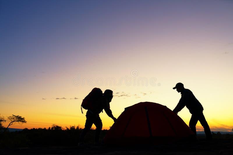 Barraca da posse da ajuda do mochileiro dois na viagem de acampamento no monte fotografia de stock