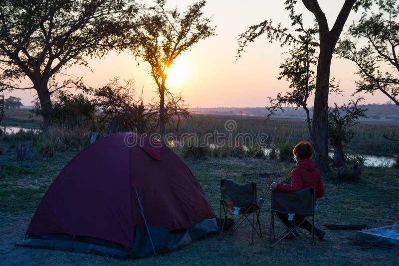Barraca de acampamento, cadeiras e engrenagem de acampamento Nascer do sol sobre beira do rio de Okavango, Namíbia Botswana Viage imagem de stock royalty free