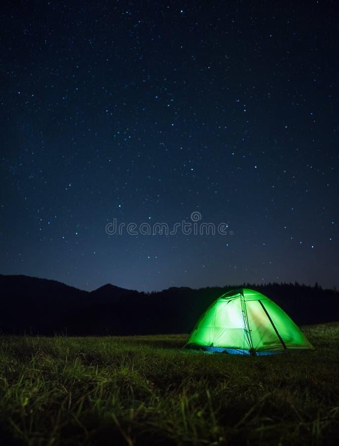 A barraca de acampamento com interior da luz está no vale da montanha sob n imagens de stock royalty free
