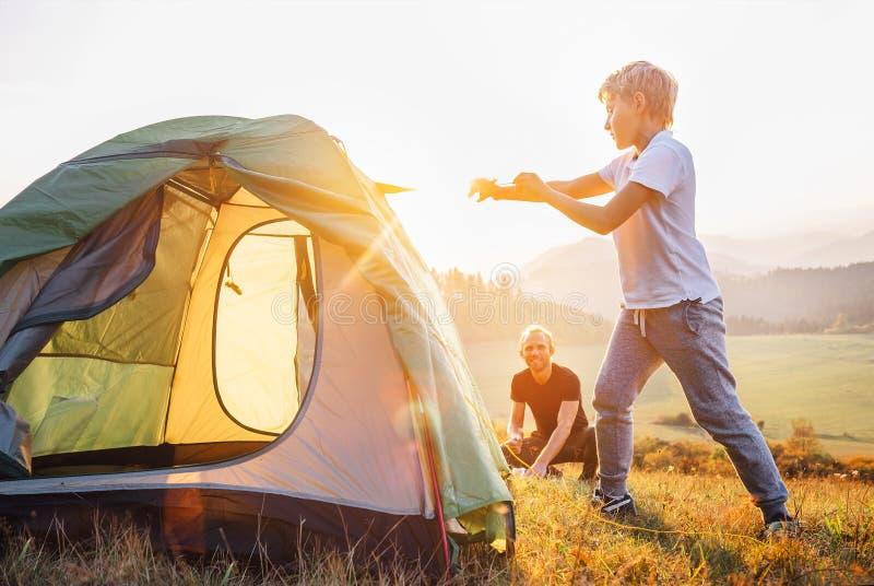 Barraca de acampamento do ajuste do pai e do filho na montanha valle do por do sol foto de stock royalty free