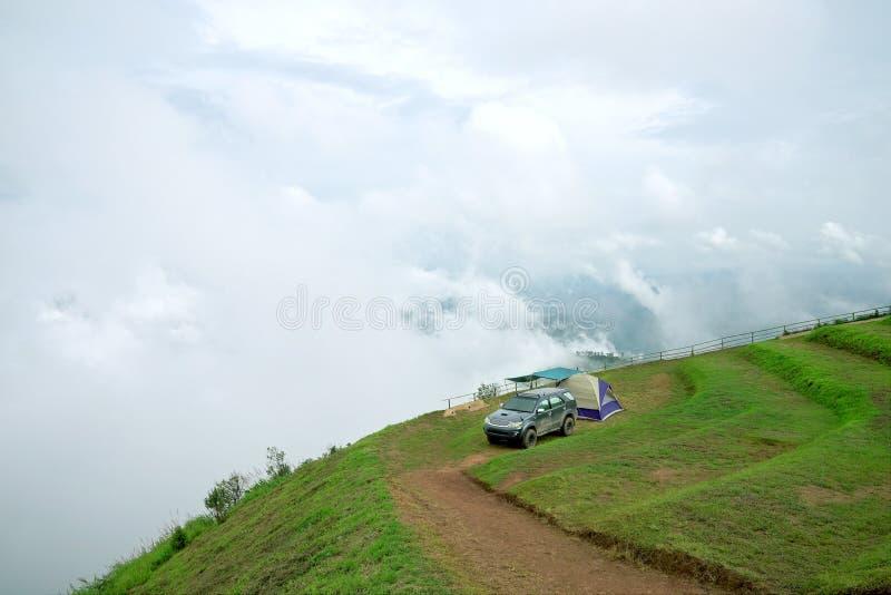 Barraca de acampamento e carro cinzento escuro no pico de montanha imagens de stock