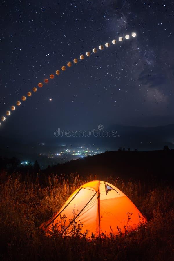 A barraca de acampamento em um vale da montanha com lua total eclipsa a trilha foto de stock