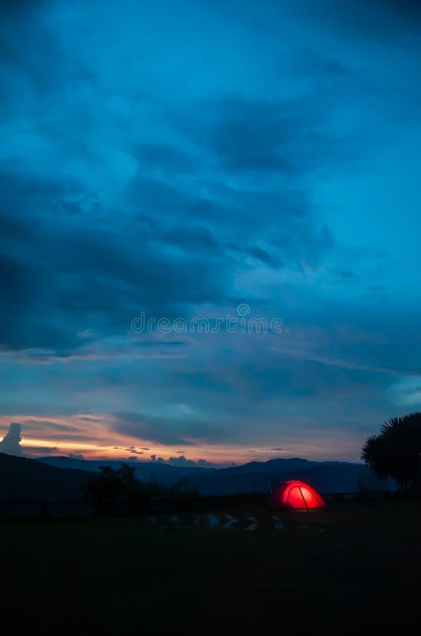 Barraca de acampamento iluminada no crepúsculo sob o céu do por do sol no pico de montanha Beira de Tailandês-Laos Phu Suan Sai N imagem de stock