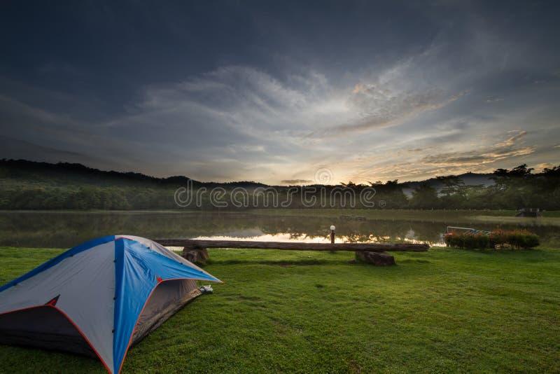 Barraca de acampamento na grama verde ao lado do lago com a floresta excedente nevoenta durante o nascer do sol imagens de stock royalty free