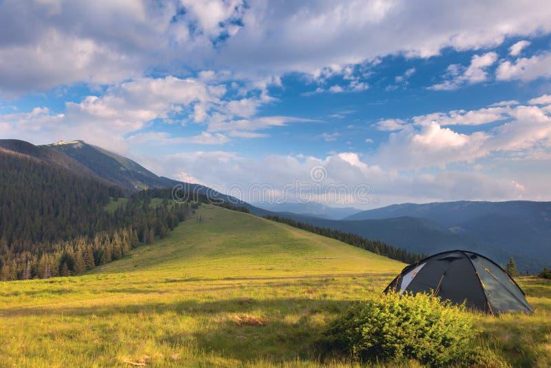 Barraca de acampamento nas montanhas verão, céu azul, nuvens e alto fotografia de stock