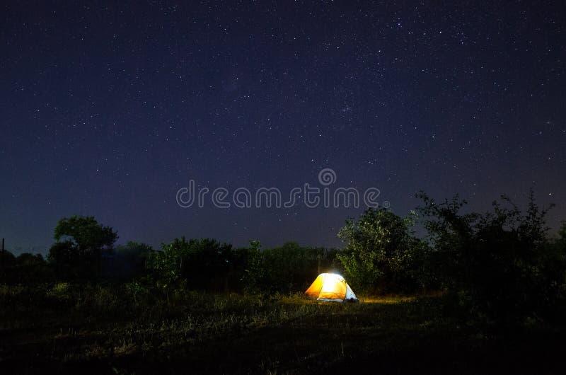 Barraca de acampamento sob o céu noturno bonito completo das estrelas Céu noturno estrelado acima da barraca turística iluminada imagem de stock royalty free