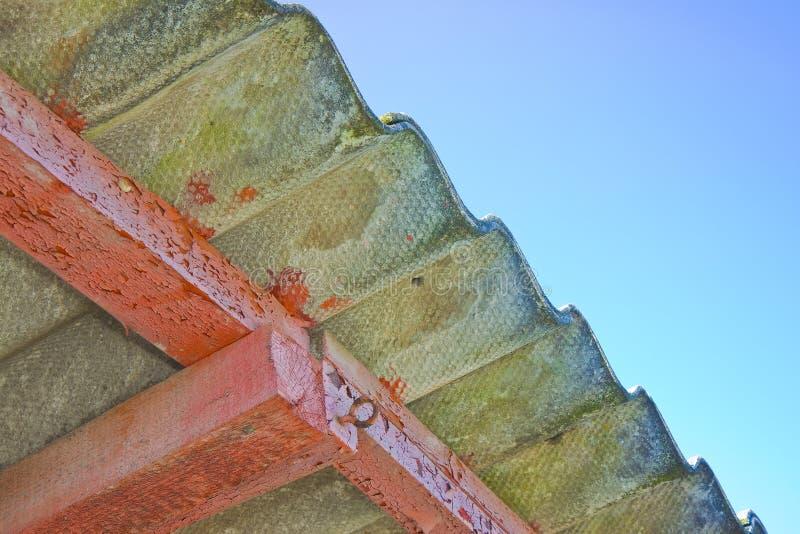 Barraca de madeira com um telhado perigoso do asbesto - um dos materiais os mais perigosos na construção foto de stock