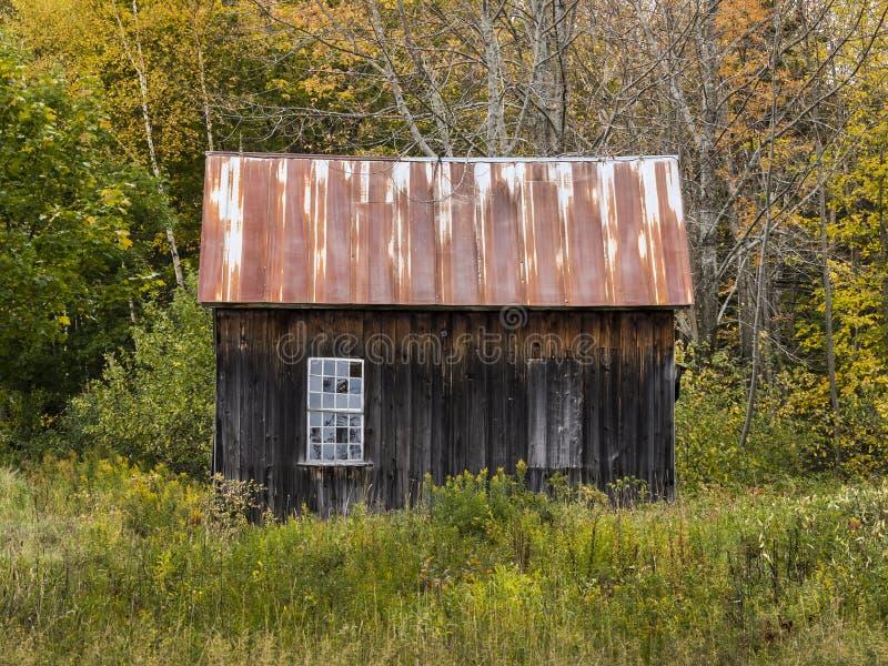 Barraca de madeira resistida velha com dois Windows - um com vidro, um ascendente fechado fotografia de stock royalty free