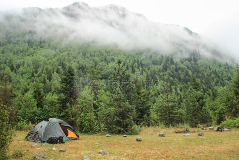Barraca e trouxa em um fundo da floresta nas montanhas em um amanhecer nebuloso imagem de stock