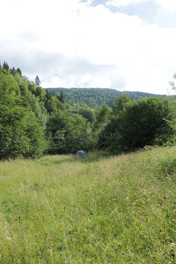 Barraca em um prado nas montanhas imagem de stock