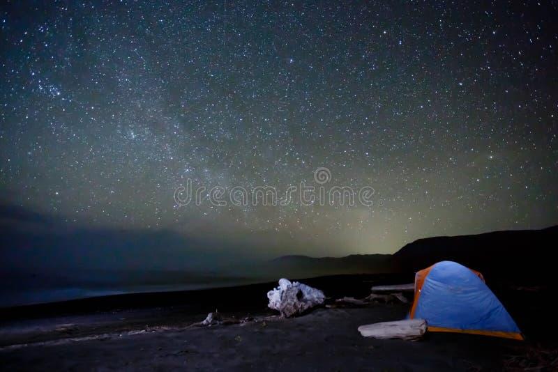 Barraca que acampa sob uma miríade de estrelas brilhantes na praia fotos de stock