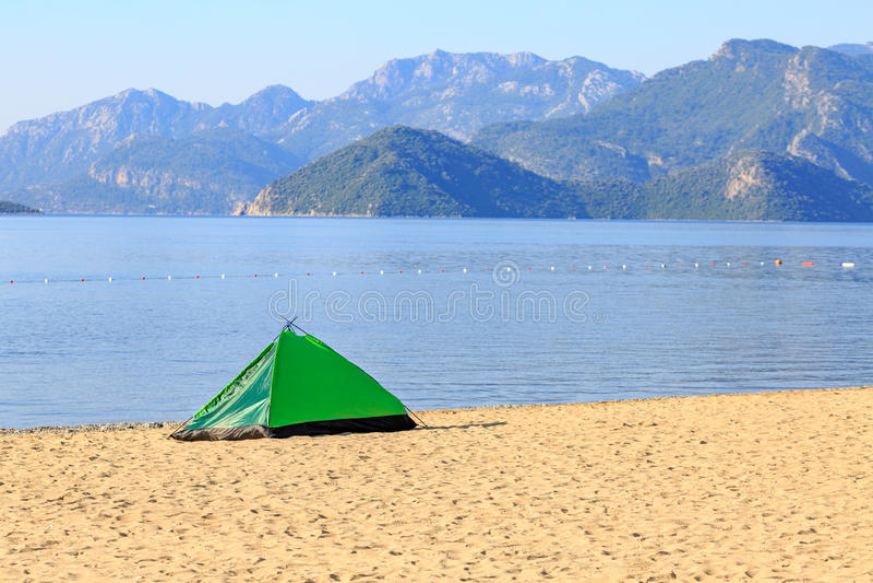 Barraca verde na praia com montanhas fotos de stock