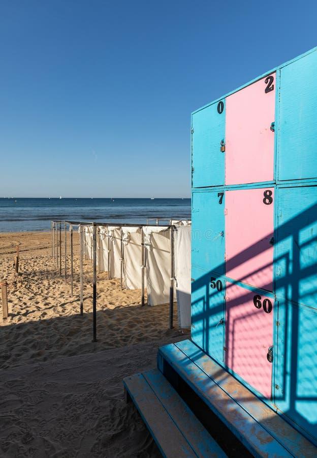 Barracas brancas e cacifos cor-de-rosa azuis na praia imagem de stock