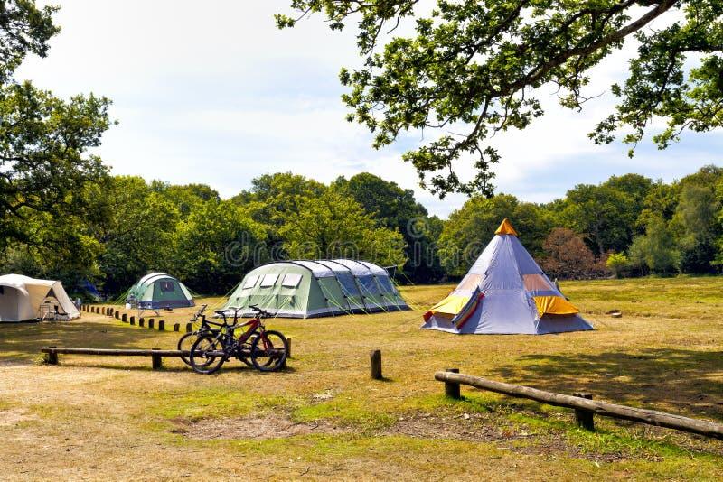 Barracas de acampamento da família em um prado perto das florestas imagens de stock royalty free