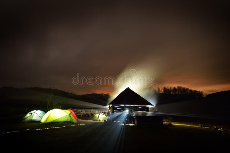 Barracas de acampamento iluminadas na noite na zona do alpin foto de stock