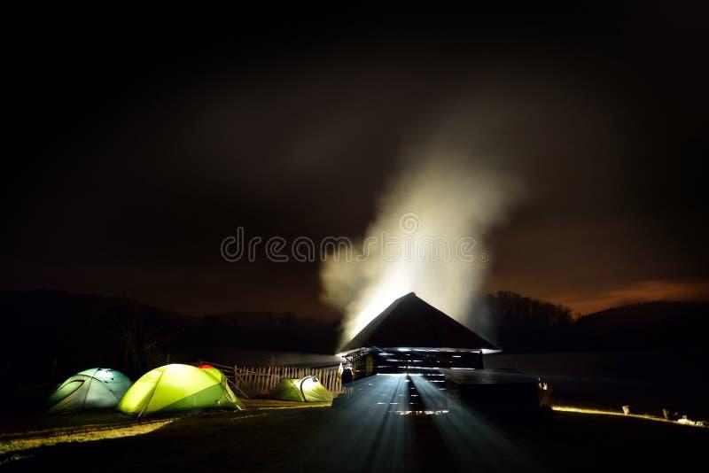 Barracas de acampamento iluminadas na noite na zona do alpin fotografia de stock royalty free