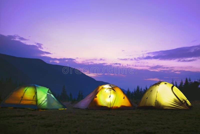 Barracas de acampamento iluminadas na obscuridade - céu azul fotos de stock royalty free