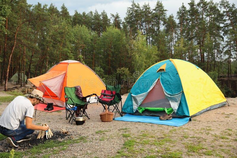Barracas de acampamento próximas da fogueira da iluminação do homem fotografia de stock royalty free